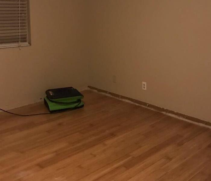 Wood floor with a green air mover working to remove the water damage.