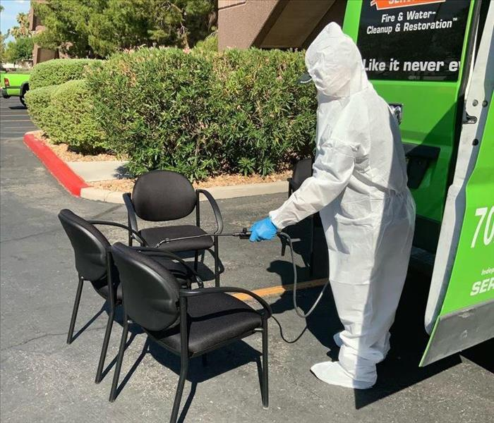person in PPE cleaning a chair.