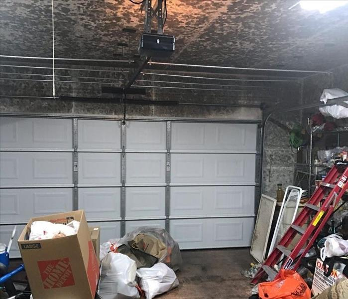 Inside of a garage with soot spots on the ceiling.