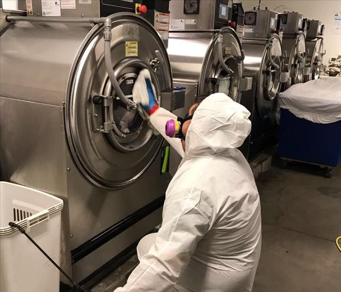 Employee cleaning a washer