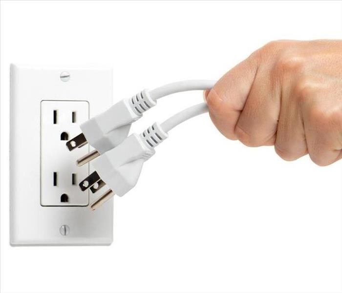 The hand of someone unplugging electrical cords